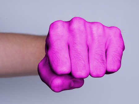 Very hairy knuckles from the fist of a man punching, pink skin photo