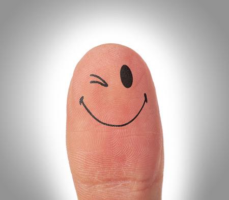 blinking: Female thumbs with smile face on the finger, eye blinking Stock Photo