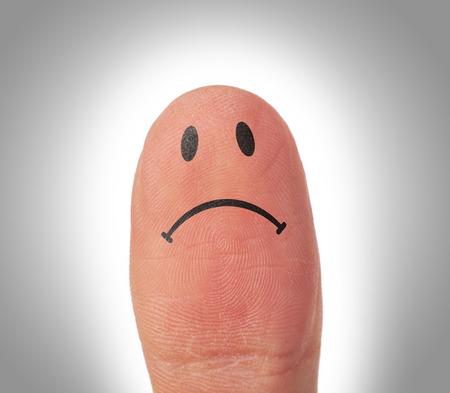 悲しいことは指に笑顔の顔を持つ女性の親指