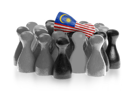 One unique pawn on top of common pawns, flag of Malaysia photo