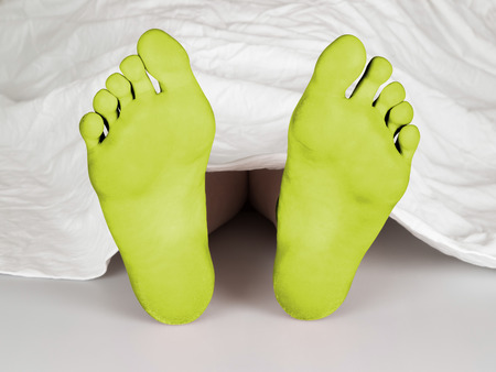 resurrect: Body under a white sheet, suicide, sleeping, murder or natural death, yellow feet Stock Photo