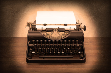 Vintage typewriter on wooden table, touch-up in retro style photo