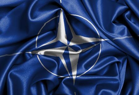 nato: Satin flag with emblem, NATO symbol close-up Editorial