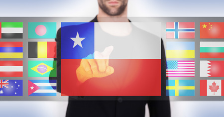 Hand pushing on a touch screen interface, choosing language or country, Chile