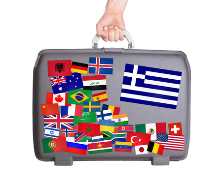Used plastic suitcase with lots of small stickers, large sticker of Greece photo