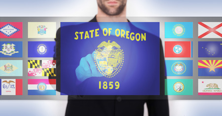 state of oregon: Hand pushing on a touch screen interface, choosing a state, Oregon Stock Photo
