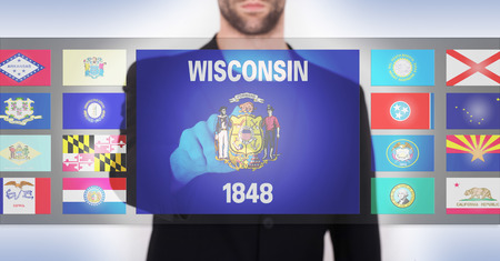 state wisconsin: Hand pushing on a touch screen interface, choosing a state, Wisconsin