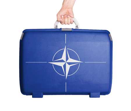 nato: Used plastic suitcase with stains and scratches, printed with flag, NATO Editorial