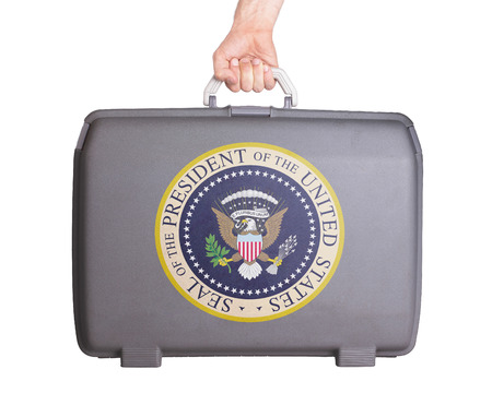 Used plastic suitcase with stains and scratches, printed with sign, presidential seal (USA)