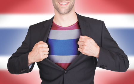 Businessman opening suit to reveal shirt with flag, Thailand photo
