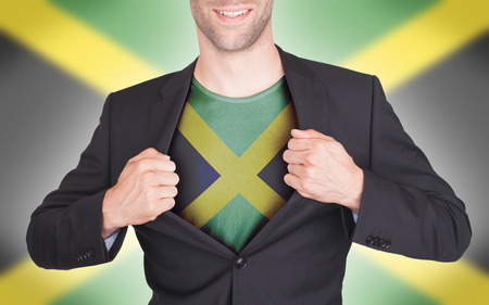 jamaican adult: Businessman opening suit to reveal shirt with flag, Jamaica Stock Photo