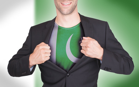 Businessman opening suit to reveal shirt with flag, Pakistan photo