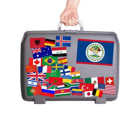 tourism in belize: Used plastic suitcase with lots of small stickers, large sticker of Belize