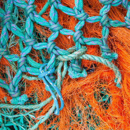 coiled rope: Abstract background with a pile of fishing nets ready to be cast overboard for a new days fishing