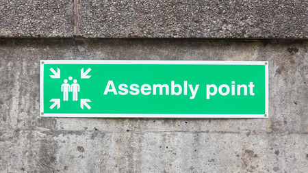 assembly point: Green plastic assembly point sign, isolated on concrete wall