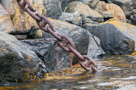 Heavy chain disappearing in the dark water, sea photo