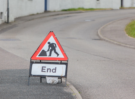 Triangular construction sign standing on footpath, end of construction photo