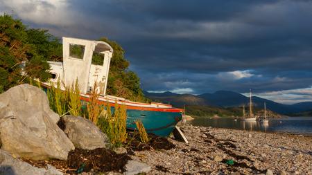 Small shipwreck at a loch with stone beach, Scotland photo
