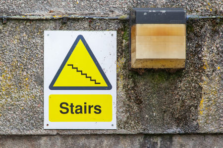 regress: Plastic sign on a concrete wall, stairs