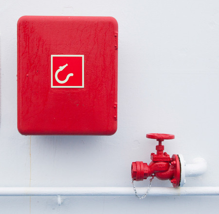 Red handled firehose outlet and a box with a firehose in it photo