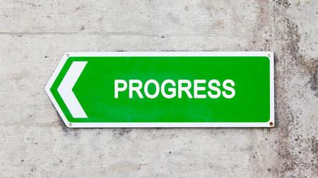 green sign: Segno verde su un muro di cemento - Progress