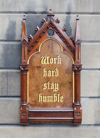 humble: Decorative wooden sign hanging on a concrete wall - Work hard, stay humble