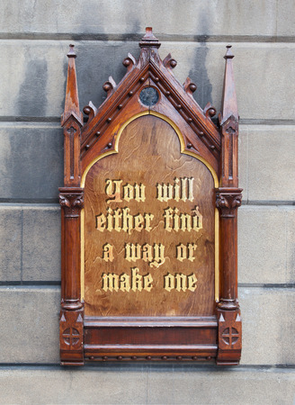 either: Decorative wooden sign hanging on a concrete wall - You will either find a way or make one