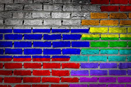 bandera gay: Textura oscura pared de ladrillo - bandera coutry y bandera del arco iris pintado en la pared - Foto de archivo