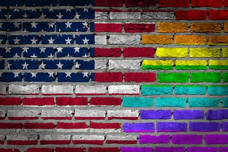 amor gay: Textura oscura pared de ladrillo - bandera coutry y bandera del arco iris pintado en la pared - Foto de archivo