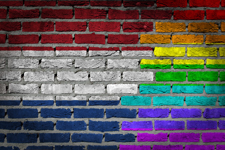 lesbo: Dark brick wall texture - coutry flag and rainbow flag painted on wall - Netherlands Stock Photo