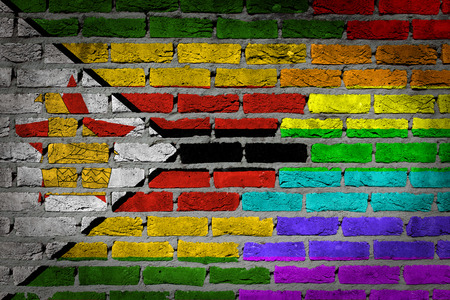 lesbo: Dark brick wall texture - coutry flag and rainbow flag painted on wall - Zimbabwe