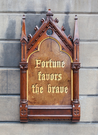 favoring: Decorative wooden sign hanging on a concrete wall - Fortune favors the brave Stock Photo