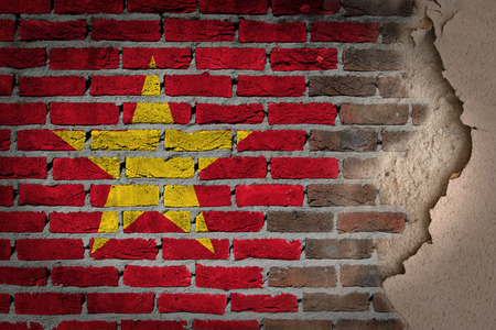 Dark brick wall texture with plaster - flag painted on wall - Vietnam photo