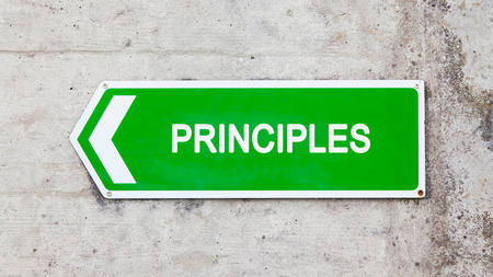 principles: Green sign on a concrete wall - Principles Stock Photo