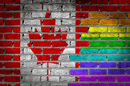 Dark brick wall texture - coutry flag and rainbow flag painted on wall - Canada photo