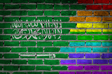 lesbo: Dark brick wall texture - coutry flag and rainbow flag painted on wall - Saudi Arabia Stock Photo