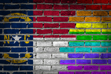 lesbo: Dark brick wall texture - coutry flag and rainbow flag painted on wall - North Carolina Stock Photo