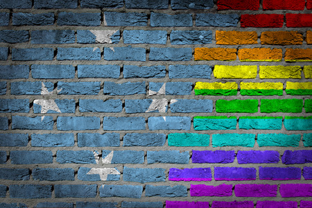 lesbo: Dark brick wall texture - coutry flag and rainbow flag painted on wall - Micronesia