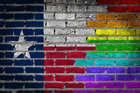 Dark brick wall texture - coutry flag and rainbow flag painted on wall - Texas Stock Photo