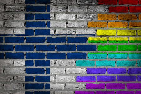 lesbo: Dark brick wall texture - coutry flag and rainbow flag painted on wall - Finland Stock Photo