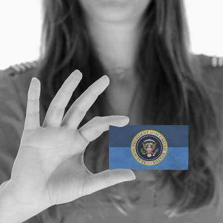 Woman showing a business card, Presidential Seal photo