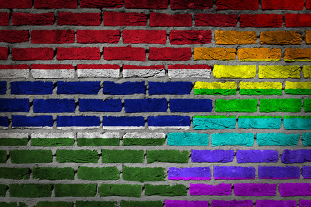lesbo: Dark brick wall texture - coutry flag and rainbow flag painted on wall - Gambia Stock Photo