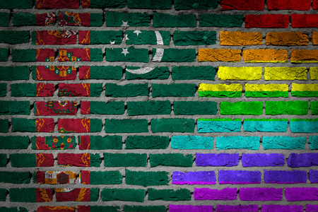 lesbo: Dark brick wall texture - coutry flag and rainbow flag painted on wall - Turkmenistan