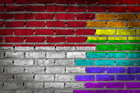lesbo: Dark brick wall texture - coutry flag and rainbow flag painted on wall - Monaco