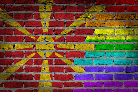 lesbo: Dark brick wall texture - coutry flag and rainbow flag painted on wall - Macedonia