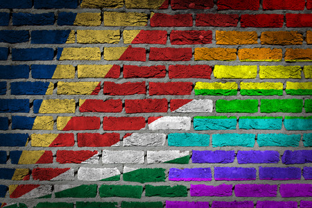 lesbo: Dark brick wall texture - coutry flag and rainbow flag painted on wall - Seychelles Stock Photo