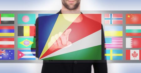 Hand die op een aanrakingsscherminterface duwen, kiezend taal of land, Seychellen