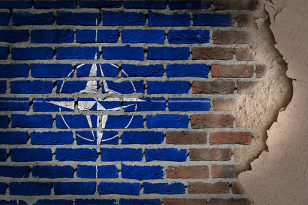 nato: Dark brick wall texture with plaster - flag painted on wall - NATO