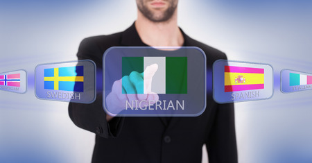 country nigeria: Hand pushing on a touch screen interface, choosing language or country, Nigeria Stock Photo