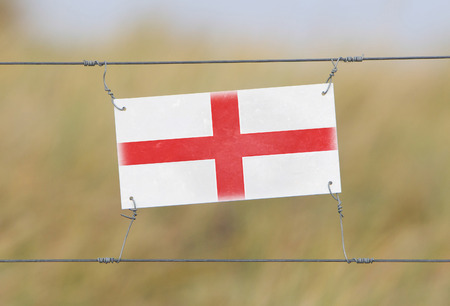 Border fence - Old plastic sign with a flag - England photo